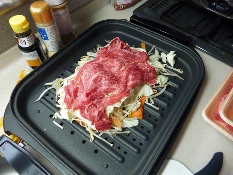 スチームプレートに野菜をしきつめ肉を上にかぶせた