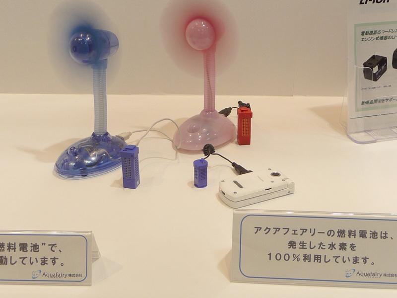 小型燃料電池「FC-STICK」を使って小型扇風機を動かしているようす。手前の携帯電話機を充電しているのは超小型モデルの「micro FC-STICK」。なお側面に細かな穴のアレイがあるのは酸素を取り入れるため。アクアフェアリーの展示ブースで撮影