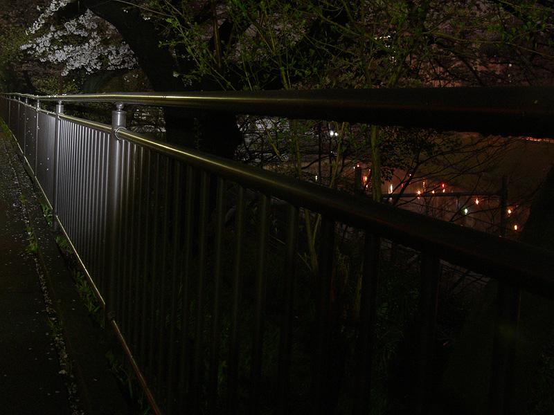 夜の公園の柵をスポットビームで照らす。10m以上先も、柵の色がわかるほど明るく照らし出された