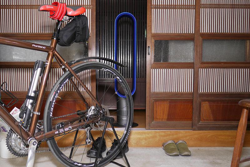 ちょっとわかりにくいが、自転車を置いている玄関で使用中のところ。冷房ナシだが、向こうの部屋は冷房があるため、タワーファンが向こうの部屋の冷気を運んでくれる。玄関で自転車イジリをするときに便利