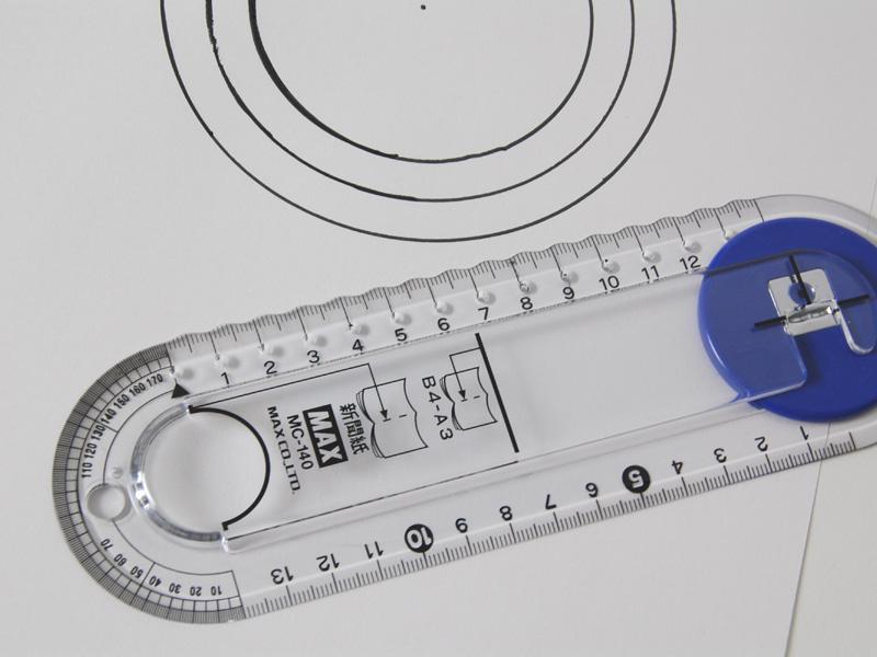 穴に2本のペン先を入れれば、1cm感覚で円が書ける簡易コンパスに