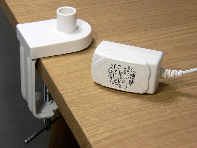 左:机などに器具を固定するための「クランプ」。 右:ACアダプターは小型で軽い