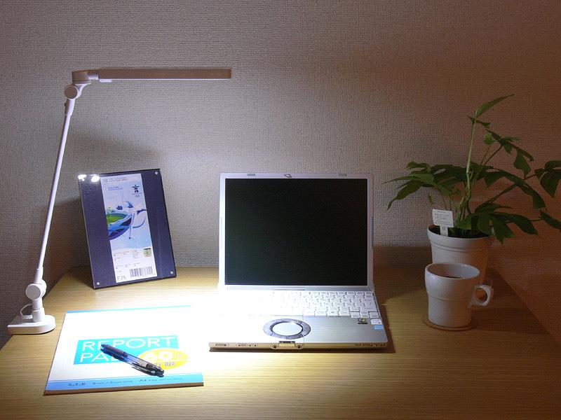 ライトをデスクに取り付けた様子。セードの位置は最大400mm。ノートブックパソコンなら、セードが画面を遮ることはない。固定式ライトは机上を広々と使える
