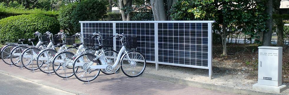 「ソーラーサイクルステーション」設置例。写真は滋賀県東近江市役所に設置したところ。右に制御盤が見える
