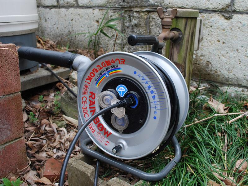 電気ドラムを使って非常用コンセントからの電気を屋外へ引っ張り出し、ポンプに接続