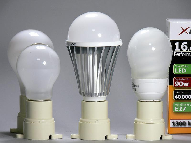 <b>【エクスレディア・昼光色</b>】<br>高さは132mm(中央)と、100W形白熱電球(後方)より23mmも背が高い。しかし口金付近のヒートシンクは36mmで白熱電球よりも4mm太い程度