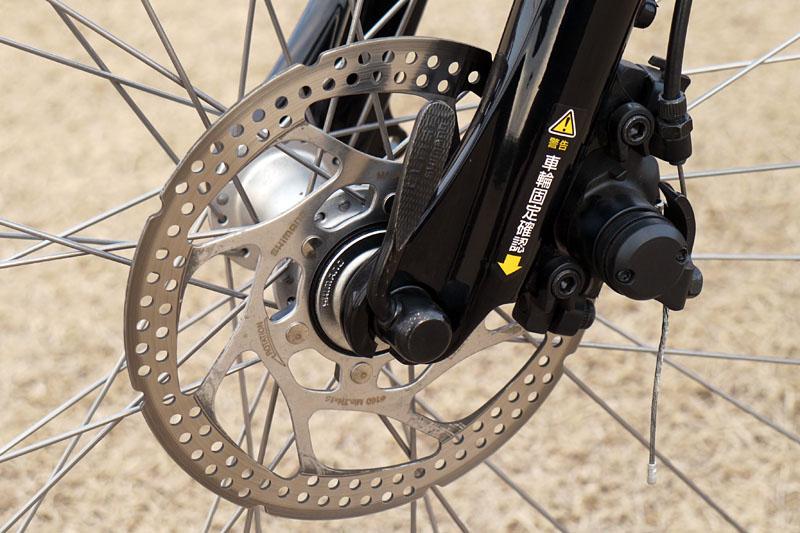 フロント側はディスクブレーキを装備。速く走れる重い電動自転車をキッチリ制動してくれる。また、写真にあるようにクイックレバーを採用していて、容易に前タイヤを外せる