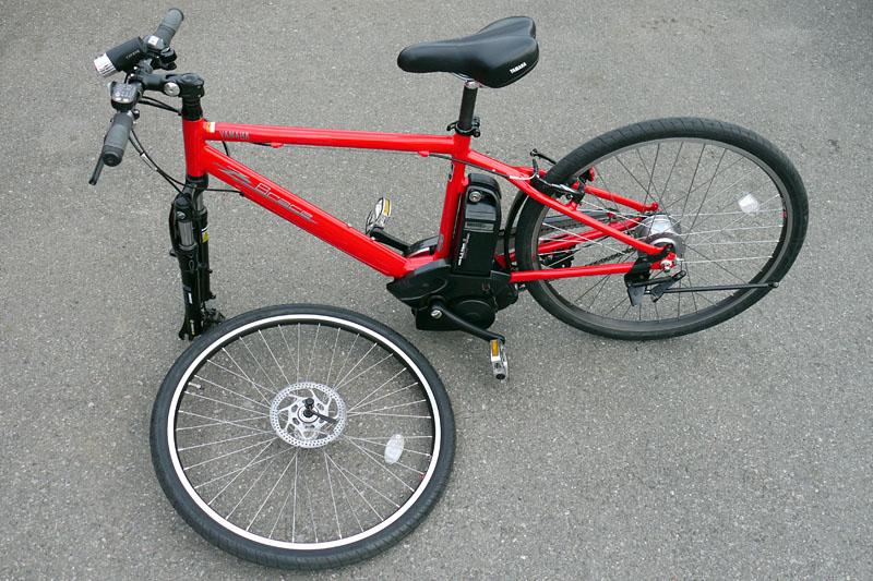 クイックレバー式なので工具を使わずにフロントタイヤを外せる。ので、クルマへの積み込みや狭い場所での保管も現実的。しかし「輪行(自転車を持って電車などに乗り込むこと)」は計23.5kgの車両重量ゆえキツい