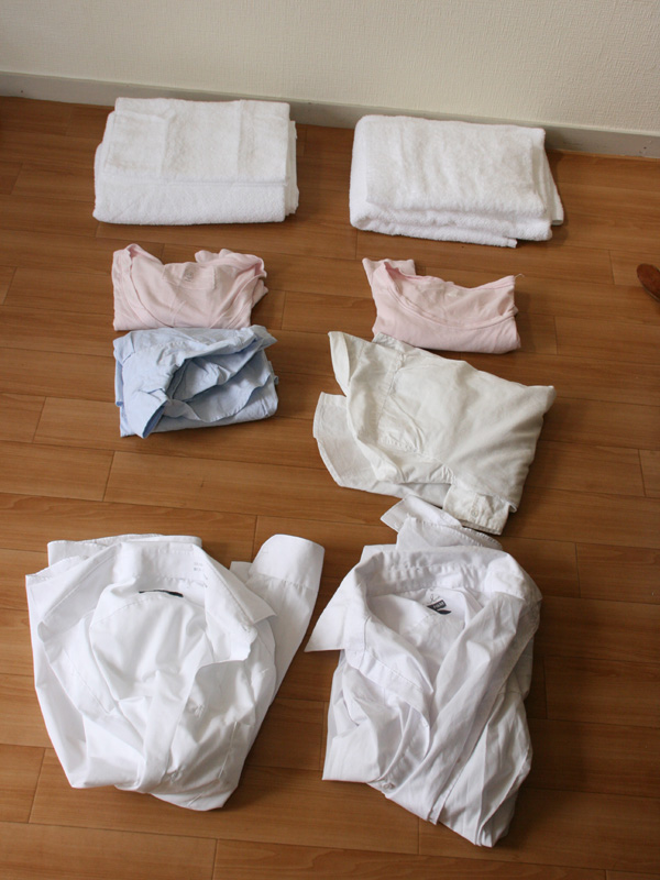 上からタオル、女性用ストレッチシャツ、綿100%のボタンダウンシャツ、男性用ポリエステル混のシャツ。天日干しと乾燥機での仕上がりの差を比べた