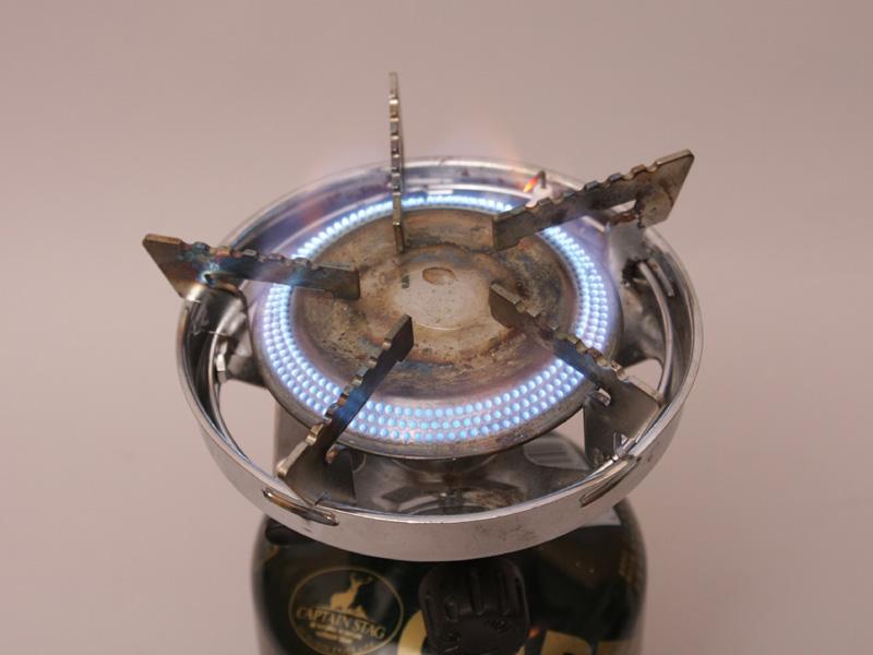 筆者愛用のコンロは炎口が円を描いているので、ナベの火の回りが均一になる一方で、いかんせん風に弱い