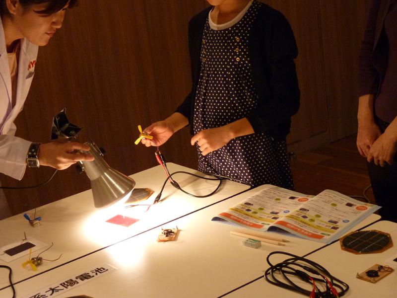 太陽光の代わりに強い光源のライトを使い、どちらの太陽電池でプロペラが回るのかを試す
