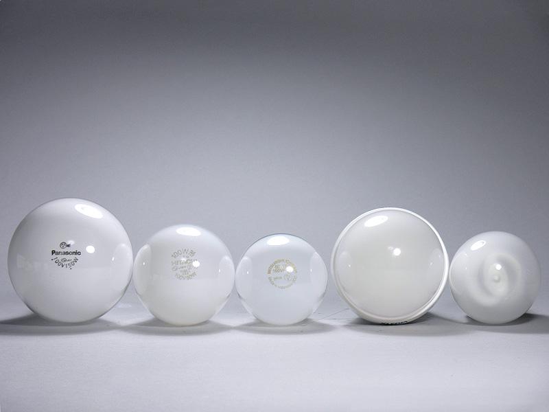 <b>【エクスレディア:昼光色</b><b>(右から2番目)</b><b>】</b><br>直径は70mmで、100W形白熱電球(左から2番目)より10mm大きいが、150W形白熱電球(いちばん左)よりも5mm小さかった。光源部は樹脂製で半透明。しかしLEDチップはほとんど透けて見えない