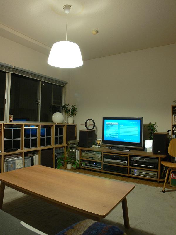 <b>【電球形蛍光灯×2 透過タイプのシェード】</b><br>白熱電球のように上部、側面へも光が広がる。しかし、テーブルはLED電球よりも暗い印象で、色被り(余計な色が加わること)によりくすんで見える