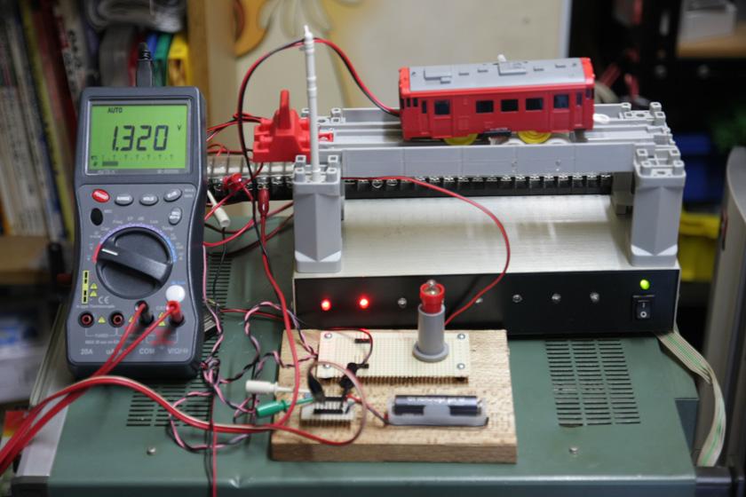 こちらがプラレールの実験装置。実は前回のエネループの実験とはワケあってテスターが変わっているが、違いによる誤差はほとんどない。なおプラレールは、その場で走り続けられるように、オリジナルのシャーシダイナモ(笑)を作り、単2電池相当の重りを入れてある