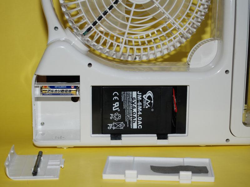 本体背面の蓋を開けた状態。左が時計で、右がバッテリ。あとで分かったが、バッテリ部分のフタは開けてはいけないと取扱説明書に書かれていた。また、左のフタのところにある黒い棒がダイヤル操作用のスティック