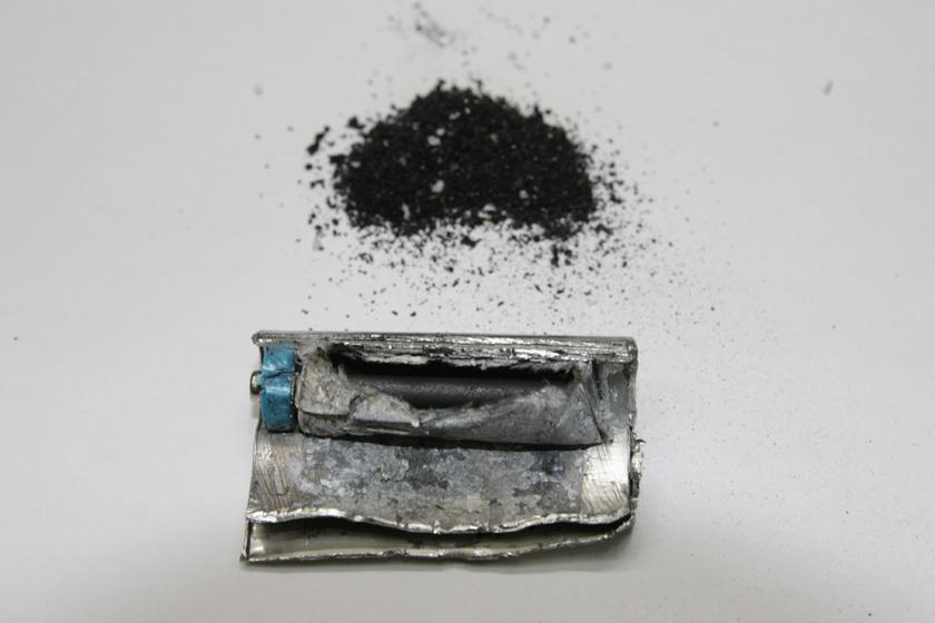 紙袋の中には、電池を安定させるための二酸化マンガンが入っている。その中央には炭素棒(炭)がプラス端子につながっている