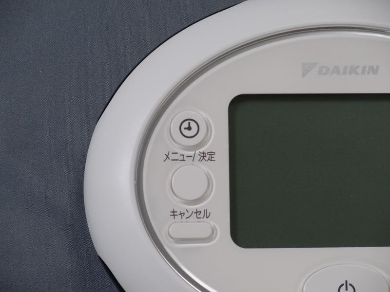 上から時計合わせボタン、メニュー/決定ボタン、キャンセルボタン
