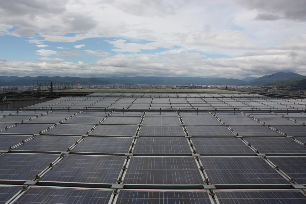 特別に屋上を見学させていただいた。一面に太陽電池パネルが広がっている。写真緑色の部分はヘリポート。写真は北側を向いて撮影したもので、かすかに京都タワーが見える