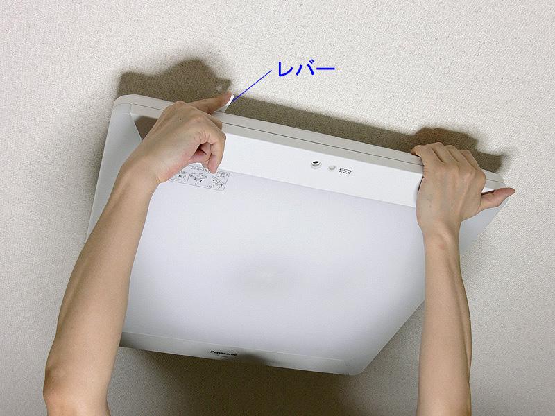 <b>【7】</b>カバーを持ち上げ水平にした状態で、本体の枠に合わせて押し上げ、2つのレバーで固定する