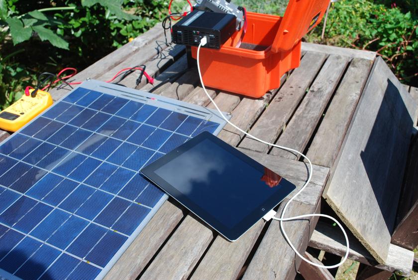 屋外で蓄電池を充電しながら、家電製品を充電してみた。まずはiPad2。USB端子でもACアダプタでも問題なく充電できた