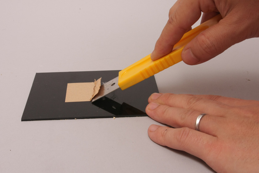 スクレイパーの柄を30~45度ほど傾けて、スコップで土を掘るような感じで油汚れに押し込んでいく。ここでは油汚れの代わりに、テープを使っている。