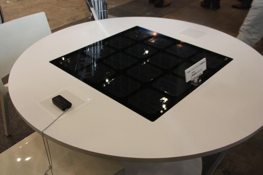 パナソニックと三洋電機による、太陽電池とQi規格の充電パッドを内蔵したテーブル。写真左のパッド部分にQi規格製品を置けば、太陽光で充電できる