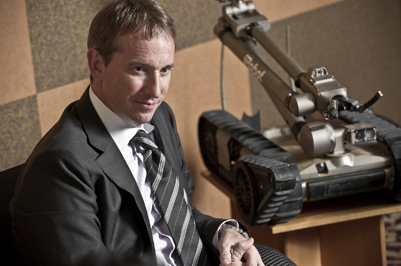 """アイロボット社創設者、現CEO(最高経営責任者) コリン・アングル氏。ボストン出身、現在44歳。米国マサチューセッツ工科大学(MIT)で最先端の人工知能研究を進めていた2名と共に、1990年にアイロボット社を設立した創設メンバー の1人。1997年には、コリン・アングルとそのチームがNASAの依頼により火星探査ロボットをデザインし、その功績により、""""NASA GROUP Achievement Award""""を受賞。その後アイロボット社は、家庭用ロボットと政府用ロボットの成長し続けるロボット産業において、「ルンバ」「パックボット」など、 数々の実用的なロボットを生み出し、世界的規模の企業に成長。彼の斬新なアイデアやリーダーシップは、アイロボット社の成長に多大な貢献をしたとして多数の専門的な賞を受賞。ロボット産業界をリードし続ける第一人者であり、今後も挑戦を続ける開拓者として評価されている"""