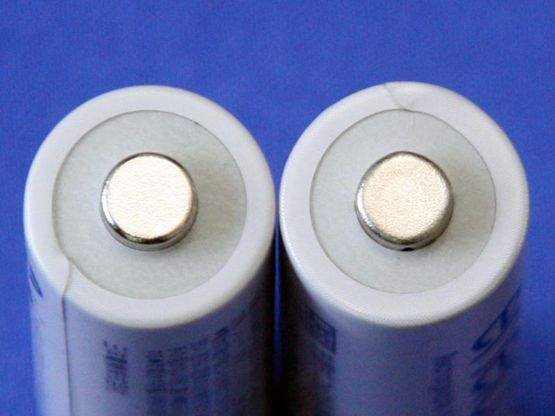 左の電池が新しいエネループで、右の電池が第2世代前半までのエネループ。プラス端子の形が、従来モデルはやや四角形のように角張っているが、新製品では真ん丸だ