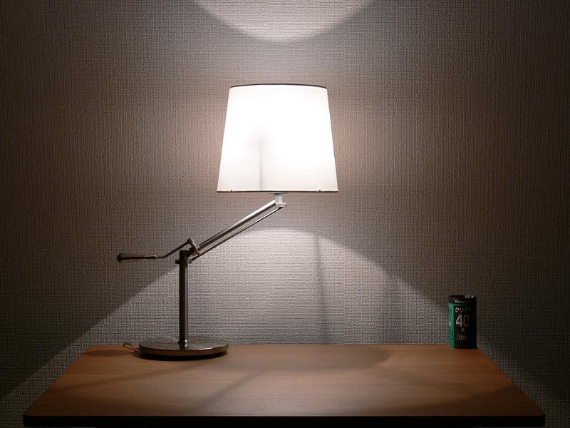 <b>【クリア電球:40/20W形】</b><br>シェードは中心からまんべんなく光っている。シェードの上下からも、ほぼ同じ明るさの光が漏れる印象があり、影の輪郭はくっきりと映る。導入線の影も見える