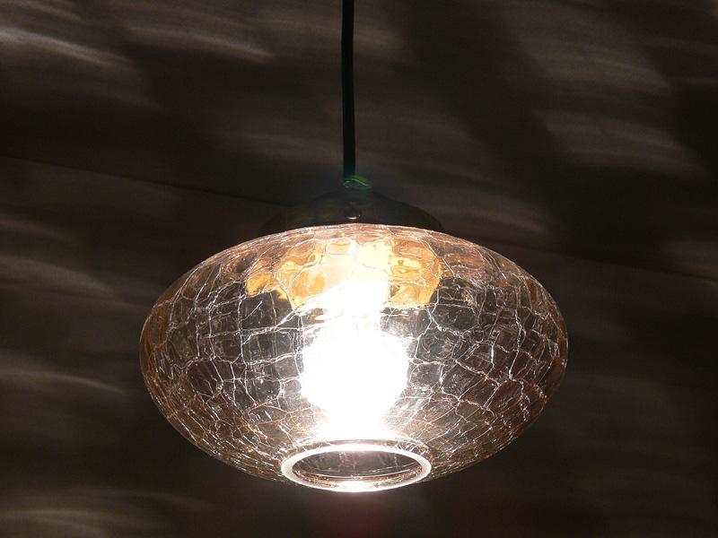 <b>【クリア電球:40W形】</b><br>透明なきらめきが強調される器具に、40Wクリア電球を取り付け、点灯した様子。ひびをあしらったガラスが満遍なく煌いている