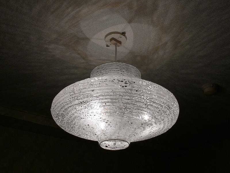 <b>【クリア電球20W】</b><br>和紙を用いたセードの孔から、フィラメントの輝きがのぞく。天井面には複雑な光と影が折り重なる