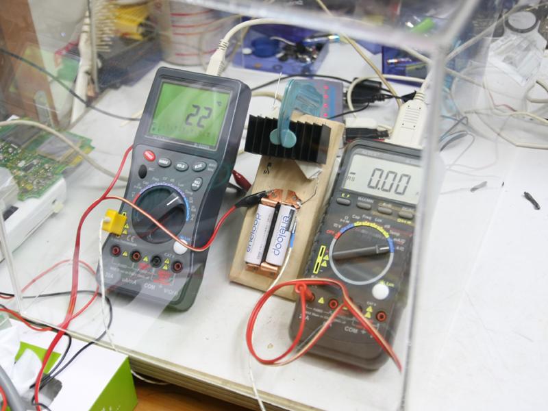 実験装置はこんな感じ。銅版と板を使って耐熱の電池ボックスを作成した。電池左側のメーターは温度を示し、右側は電流を示している。机が汚いのはゴメンナサイ!