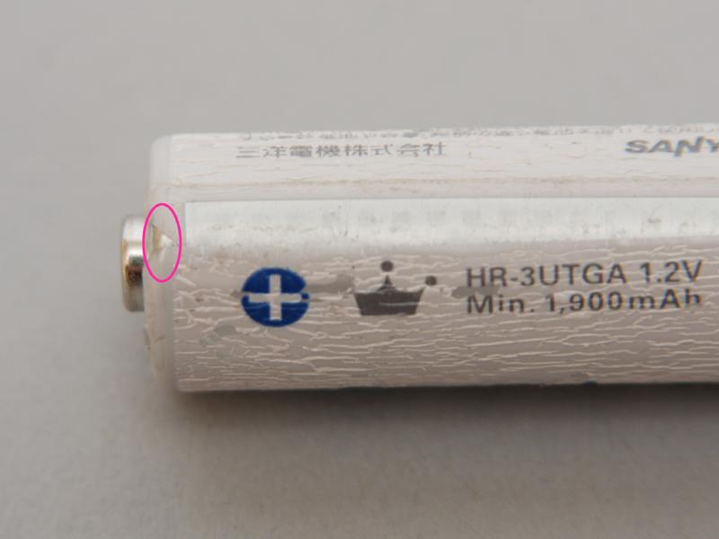 シールが収縮してプラス端子に近い場所から、マイナス端子につながる金属ケースが露出(○印のところ)してしまっている