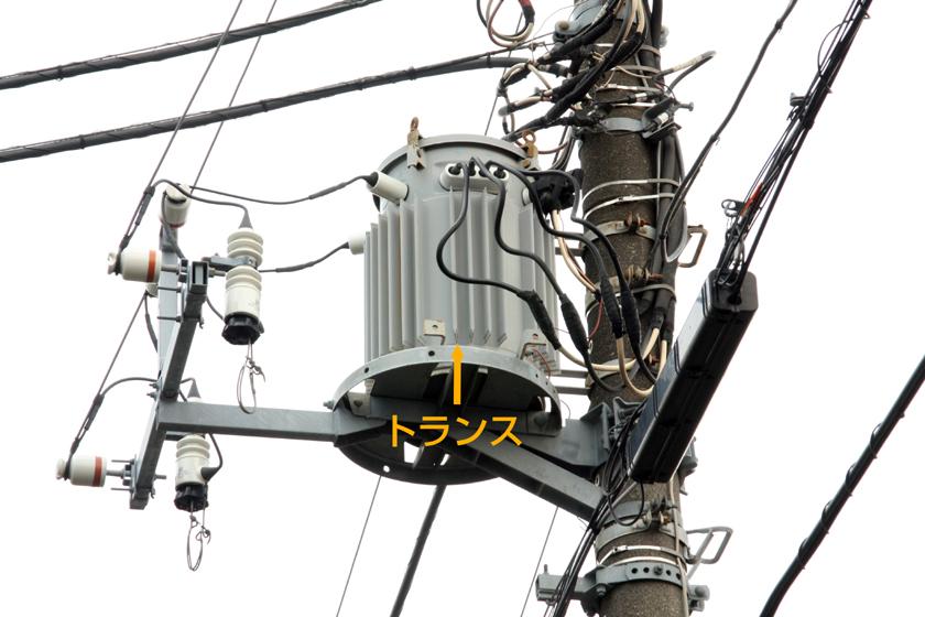 電柱の上に乗っているトランスと呼ばれる装置。近所の電柱間の電線には6,600Vの電気が流れているので、トランスで100Vや200Vに電圧を下げている。極論するとACアダプタのようなもの。その中などに避雷器が取り付けられている