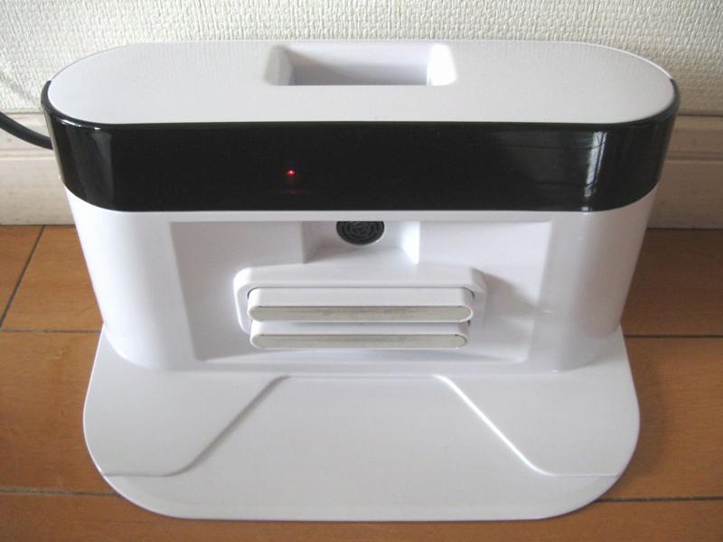 充電台。ACアダプターをコンセントにつなぐと充電ランプが赤く点灯する。黒い帯状の部分が赤外線送信部、その下の丸い部分が本体の接続位置を確認するための超音波受信部となっている