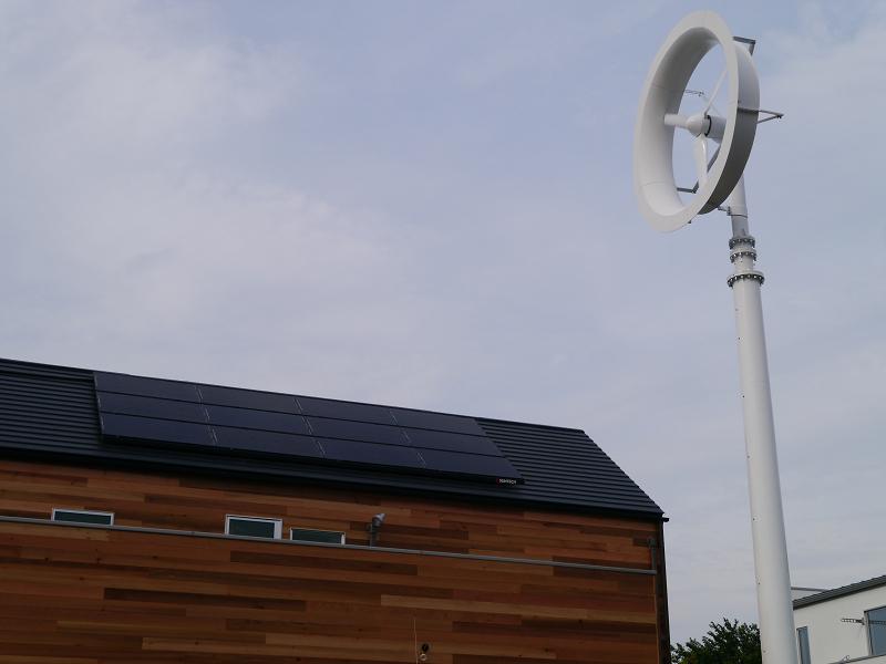 風力発電システムと屋根の上に設置された太陽光発電システム
