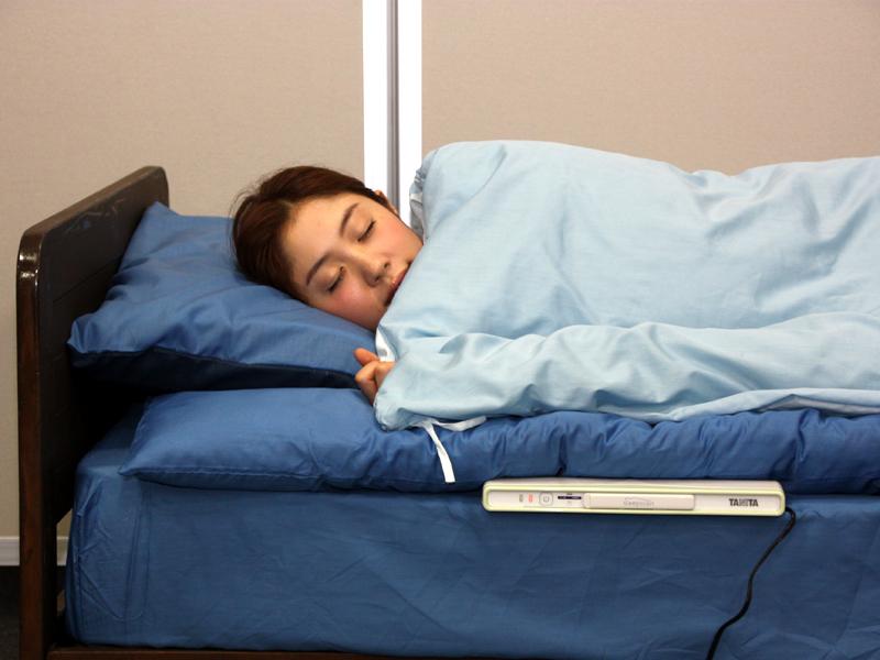 身体の上下方向に垂直に、睡眠計の上辺が肩の位置にくるように寝る