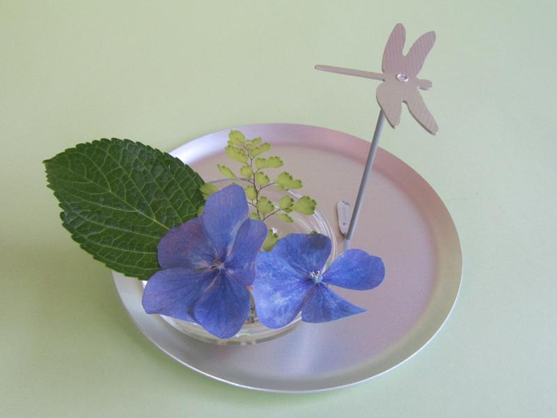 小さなガラスの器に花を入れて皿の上に。とんぼが花を見て休んでいるよう。心和むワンシーンのできあがり