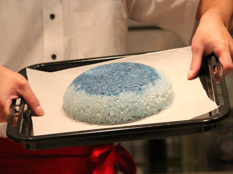 米をしっかり攪拌するので、釜内の米が混ざり炊きムラが少ないという。写真は青く着色した米と普通の米を混ぜて炊いたもの。攪拌工程なしで炊きあげると、青い米が下に溜まってしまっているのがわかる