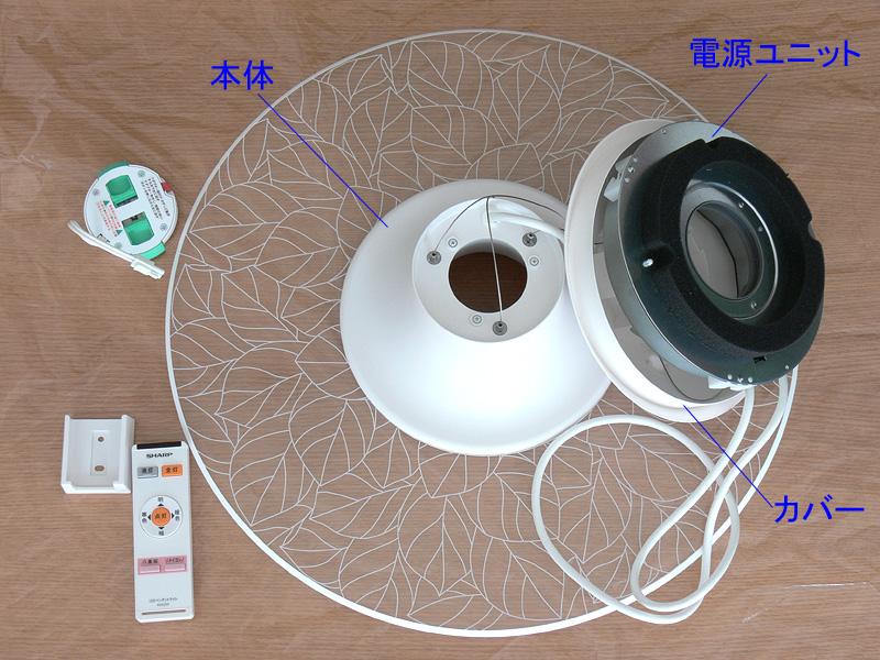 開梱した器具。左上から、アダプター、リモコンホルダー、リモコン。中央が3本のワイヤーとケーブルで繋がっている本体とカバー、電源ユニット。他に導光板を拭くクロスも同梱されている