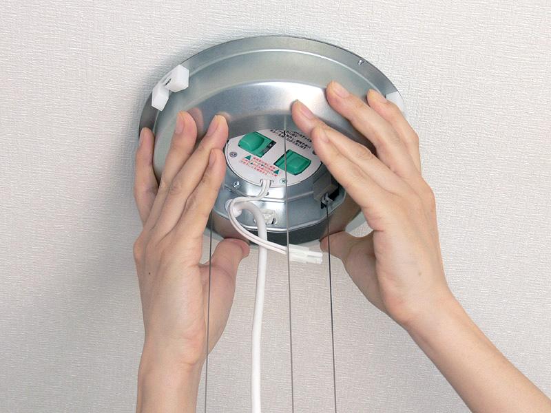 <b>【2】</b>アダプターから出ているコネクターを、電源ユニットの本体の中央に通しながら、「カチッ」と音がするまで押し上げて取り付ける。電源ユニットとカバー、本体はワイヤーとケーブルで繋がっているので、取り扱いは十分注意