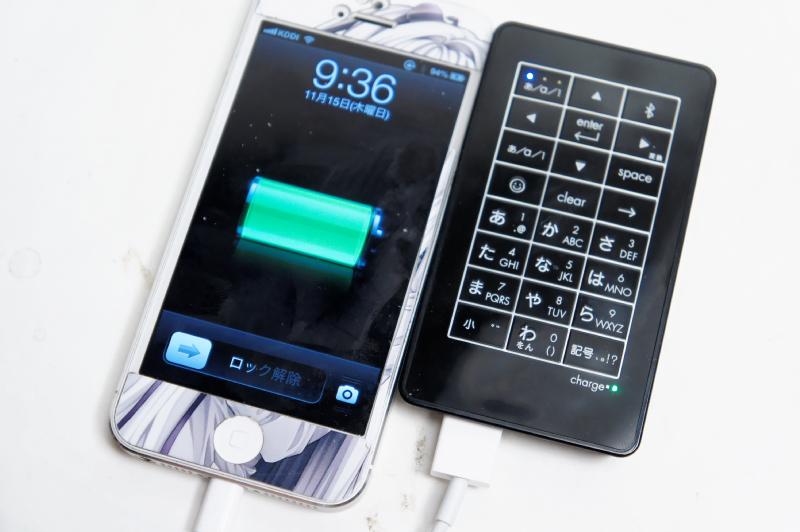 iPhone 5を充電しているところ。放電時は本体右下の緑ランプが点灯する。またBluetooth接続しながらの充電にも対応