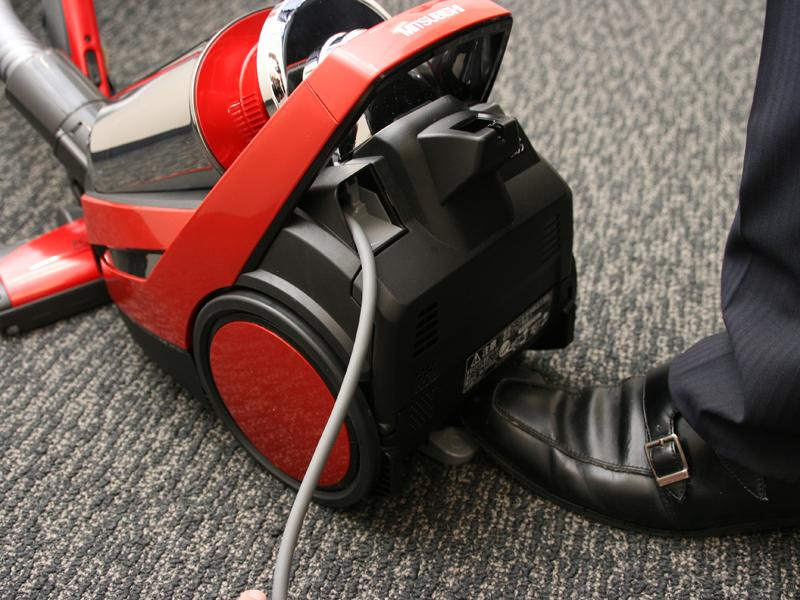 足でコードリールのスイッチを押せる「大型コードリールボタン」を本体後部に搭載する