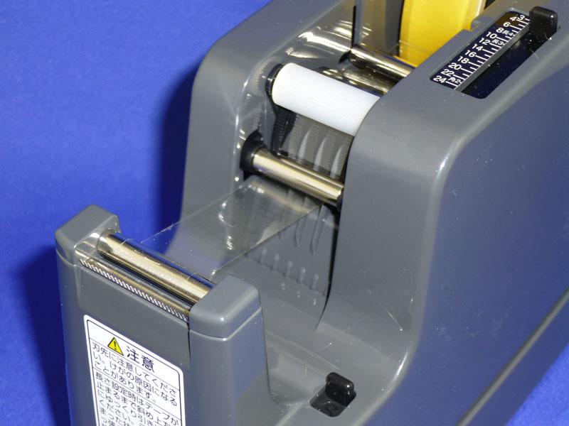 テープは白い補助ローラーと、その下で金属色のリセットローラーの下を通る