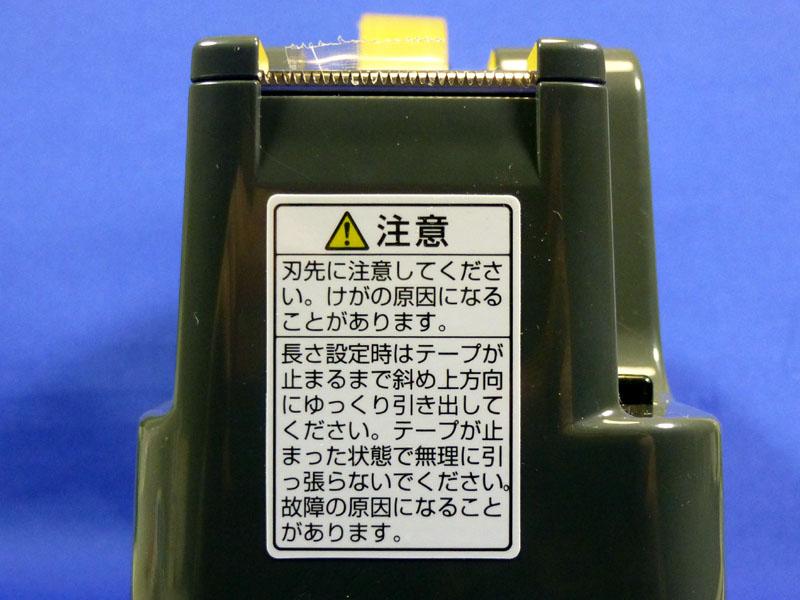 カッター刃のそばに貼られている注意。長さ設定してあるときは、テープを斜め上方向に引っ張れと書かれている
