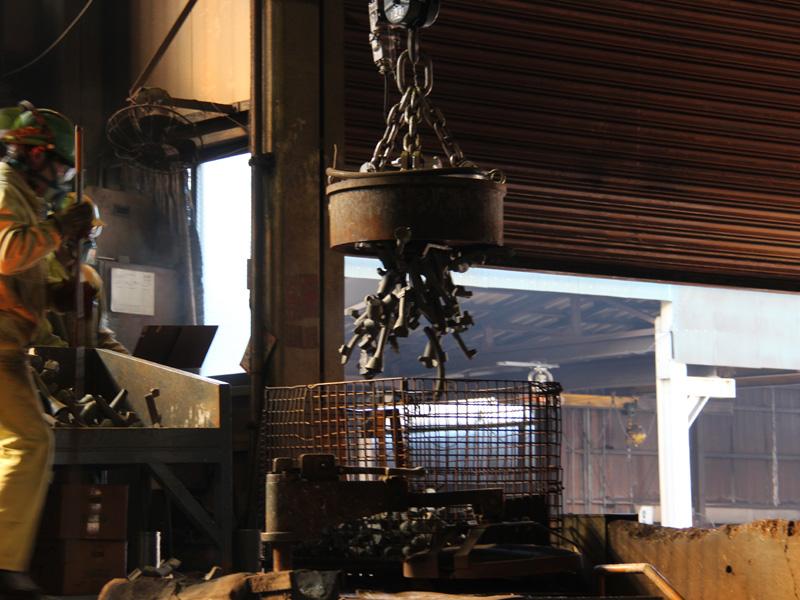 巨大な電磁石を使って炉の中に鉄を入れる