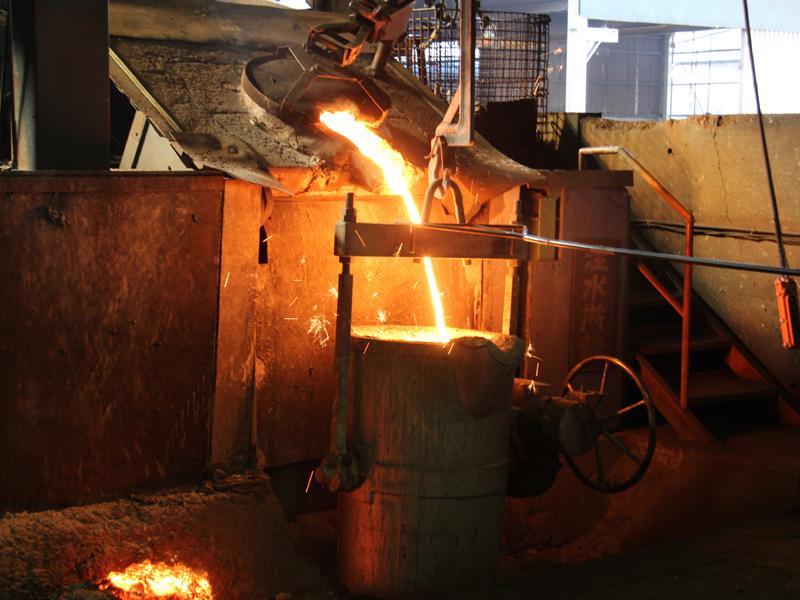 炉を引き上げ500kgの鉄を容器に移し替える。3mほど離れていても、間近で焚き火に当たっているように熱い