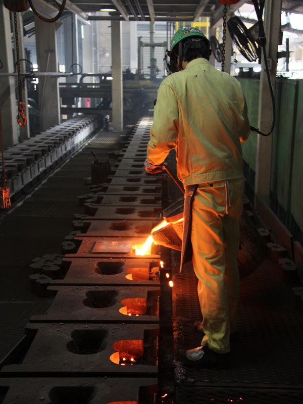 鋳型1つ1つに鉄を流し込んでいく。鋳型のあちこちから炎が上がるほど高温