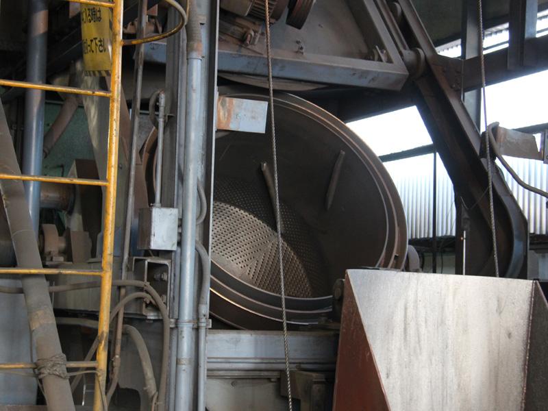 先ほどの砂だらけの内釜を、写真のドラム式洗濯機のような機械に入れてキレイにする。写真ではドラムのフチに隠れてしまっているが、中に真っ黒な内釜が30個ほど入っている。回転中は写真上部のフタが閉じる