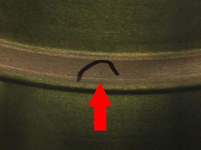左の写真のマジック部を、デジタル処理してズームした写真。0.1mmほどの気泡が2つあるだけだ。えーーーーっ! これで不合格なの!